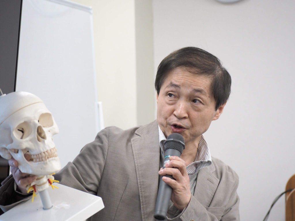 頭蓋模型を使って顎関節の説明をする佐藤嘉則院長
